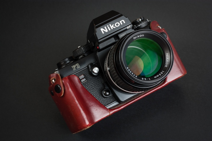 Nikon F3 in leather half case with Nikkor 105mm f/2.5 and HP prism.