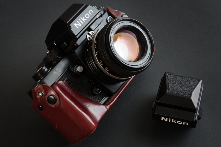 Nikon F3 in leather half case with Nikkor 50mm f/1,4 and HP prism. Waist level finder next to it.